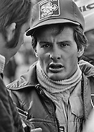 A patient Gilles Villeneuve answers reporter's questions before the start of the 1979 US Grand Prix. Villenueve would go on to win the Grand Prix ensuring his second place ranking in the 1979 World Driving Championship, giving Ferrari both first and second in the Driver's Championship, and also guaranteeing Scuderia Ferrari would win the World Constructor's Championship with the 312 T4.<br />