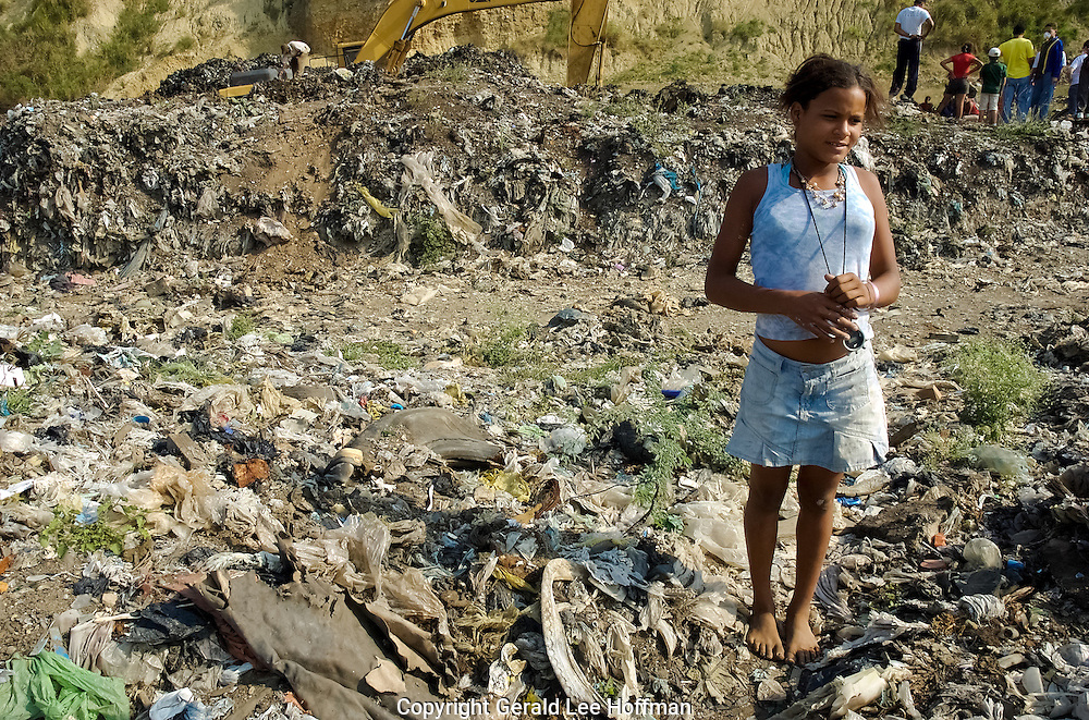 Looking For Shoes. This 13 year old girl was wondering the burning dump in La Mosca looking for a new pair of shoes. I was wearing thick soled boots. There were metal shards, broken glass and nails everywhere.