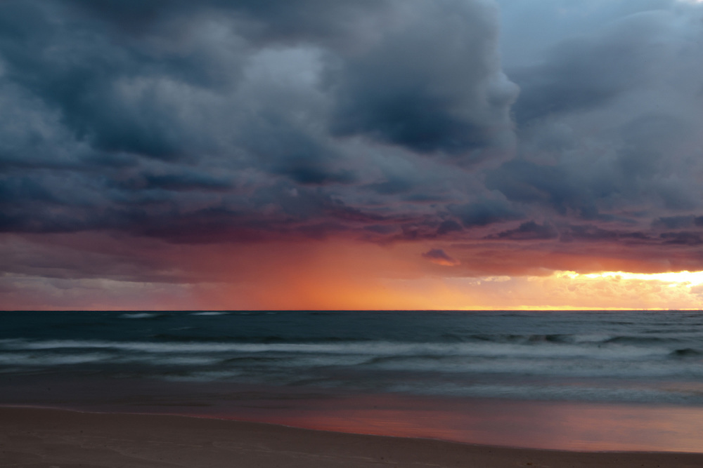 A rainstorm sweeps across Lake Michigan at sunset.