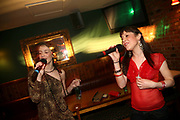 Two young women singing Karaoke at Varsity, Cardiff, Wales, UK 2006