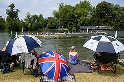 © Licensed to London News Pictures. 04/07/2018. Henley-on-Thames, UK. People shelter form the sun underneath umbrellas on day one of the Henley Royal Regatta, set on the River Thames by the town of Henley-on-Thames in England. Established in 1839, the five day international rowing event, raced over a course of 2,112 meters (1 mile 550 yards), is considered an important part of the English social season. Photo credit: Ben Cawthra/LNP