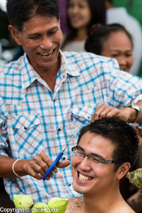 "21 JULY 2013 - BANGKOK, THAILAND:  A young man's family cuts his hair before he became ordained as a Buddhist monk at Wat Benchamabophit on the first day of Vassa, the three-month annual retreat observed by Theravada monks and nuns. Men frequently enter the monastery and become monks for Vassa. On the first day of Vassa (or Buddhist Lent) many Buddhists visit their temples to ""make merit."" During Vassa, monks and nuns remain inside monasteries and temple grounds, devoting their time to intensive meditation and study. Laypeople support the monastic sangha by bringing food, candles and other offerings to temples. Laypeople also often observe Vassa by giving up something, such as smoking or eating meat. For this reason, westerners sometimes call Vassa the ""Buddhist Lent.""       PHOTO BY JACK KURTZ"