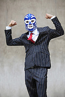 Young businessman flexing muscles in wrestling mask over gray background