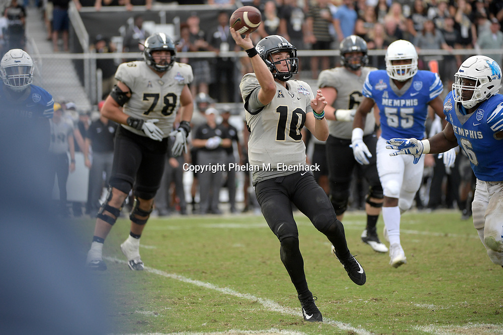 Central Florida quarterback McKenzie Milton (10) throws a pass in front of Memphis linebacker Genard Avery (6) during the second half of the American Athletic Conference championship NCAA college football game Saturday, Dec. 2, 2017, in Orlando, Fla. Central Florida won 62-55. (Photo by Phelan M. Ebenhack)