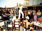 Girl dancing on a table in a beach bar Ibiza 1999