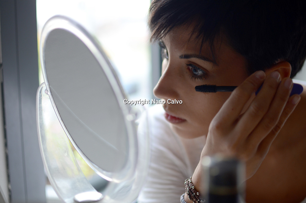 Young woman applying makeup and reflected on a mirror