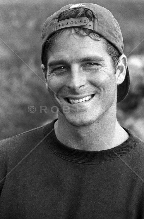 man smiling while wearing a turned around baseball cap
