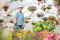 Portrait of happy man carrying watering can in greenhouse