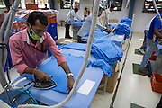 A man irons a C & A T-shirt in a Pratibha Syntax factory, where organic cotton is being used to make clothes, Indore, India.