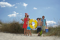 Parents with three children (6-12) carrying beach accessories