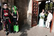 Twee goths wachten bij de Domtuin op een poserend bruidspaar. In Utrecht komen goths uit heel Europa bij elkaar voor het jaarlijkse festival Summer Darkness. Tijdens het driedaags festijn zijn er onder andere optredens van bands, een markt en een modeshow. Het is ook een kwestie van zien en gezien worden.<br /> <br /> Two goths are meeting a wedding couple at the Summer Darkness festival. During the festival goths from all over Europe are coming to Utrecht to meet and enjoy music, a market, a fashion show and more.