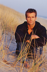 handsome man in tall beach grass in East Hampton, NY