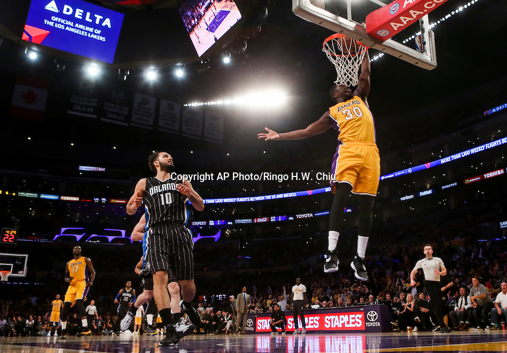 Orlando Magic forward Evan Fournier, left, looks on as Los Angeles Lakers forward Julius Randle dunks during the second half of an NBA basketball game Tuesday, March 8, 2016, in Los Angeles.  Lakers won 107-98. (AP Photo/Ringo H.W. Chiu)