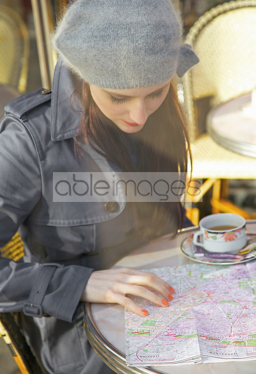 Young woman at cafe looking over a map