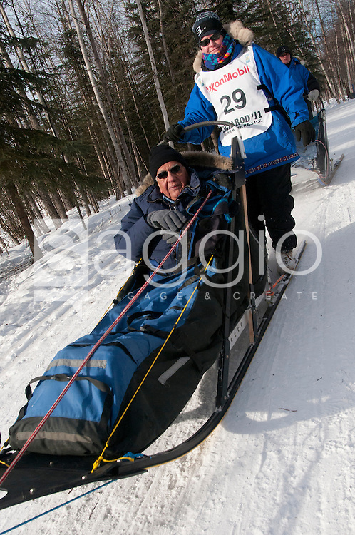 Musher Judy Currier and  Iditarider Marty Vega ride along the Chester Creek Trail during the 2011 Iditarod Ceremonial Start.