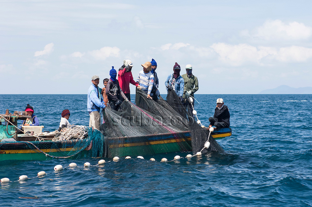 A team of fishermen on a small fishing boat, hauling in a large fishing net, Mabul Island, Sabah, Malaysia.