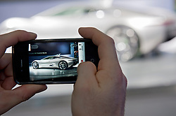 New Jaguar sports car viewed through camera phone at the Paris Motor Show 2010