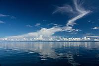 Glassy ocean and blue sky near Kwatisore, Cenderawasih Bay, Western Papua, Indonesia