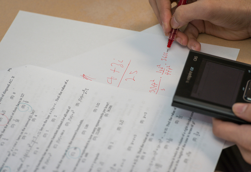 Saul Cantu works with students to solve Algebra 2 equations at Young Men's College Preparatory Academy, February 19, 2014.
