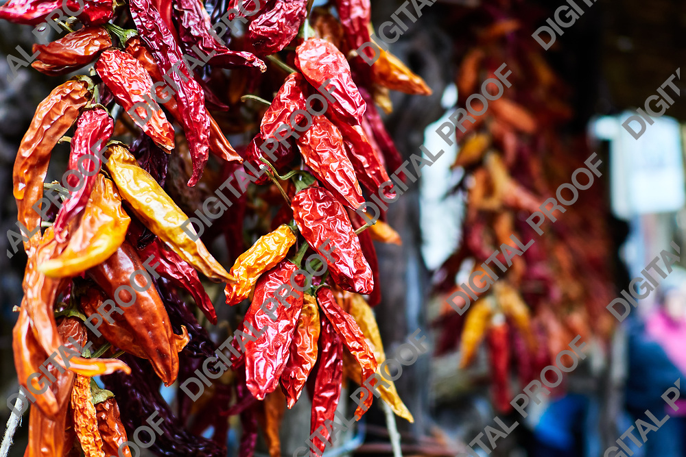 Closeup of dried red and yellow peppers hanging from a street stall
