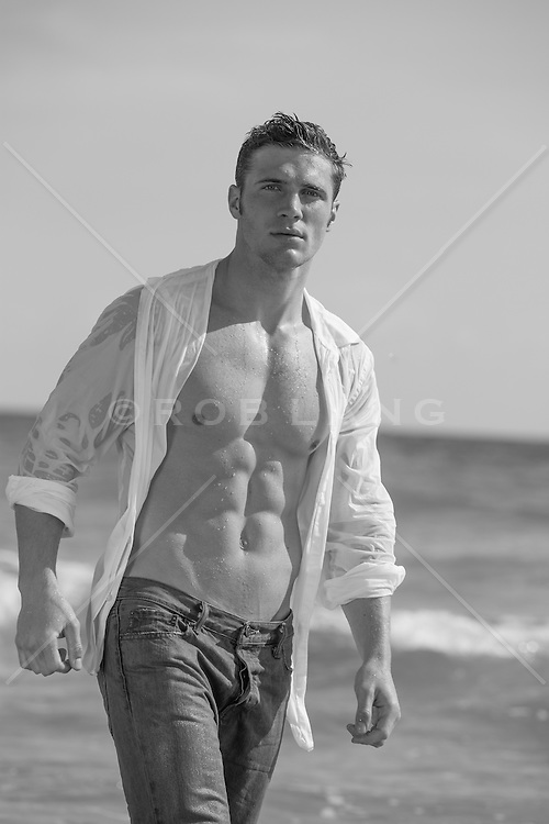 hot man with a wet open shirt at the ocean