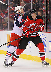 Feb 27, 2014; Newark, NJ, USA; Columbus Blue Jackets left wing Matt Calvert (11) hits New Jersey Devils defenseman Mark Fayne (7) during the second period at Prudential Center.