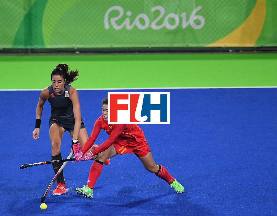 Netherland's Naomi van As (L), and China's Liang Meiyu stretch for the ball during the women's field hockey China vs Netherlands match of the Rio 2016 Olympics Games at the Olympic Hockey Centre in Rio de Janeiro on August, 10 2016. / AFP / MANAN VATSYAYANA        (Photo credit should read MANAN VATSYAYANA/AFP/Getty Images)
