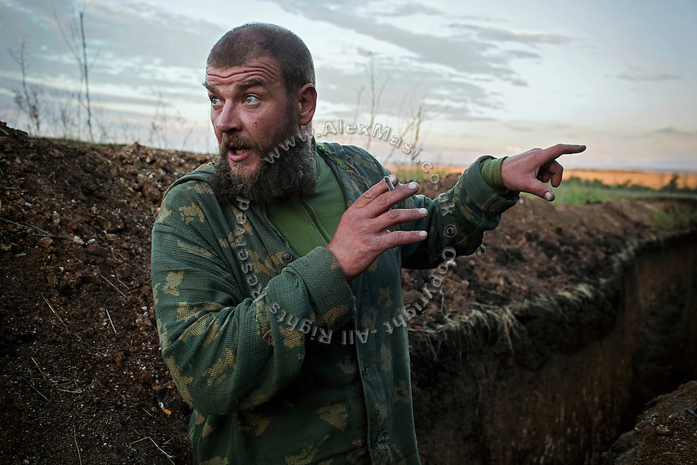 A soldier is discussing the morning's enemy movements while standing in the trenches on the frontline of Hranitne, near Mariupol, southeast Ukraine.