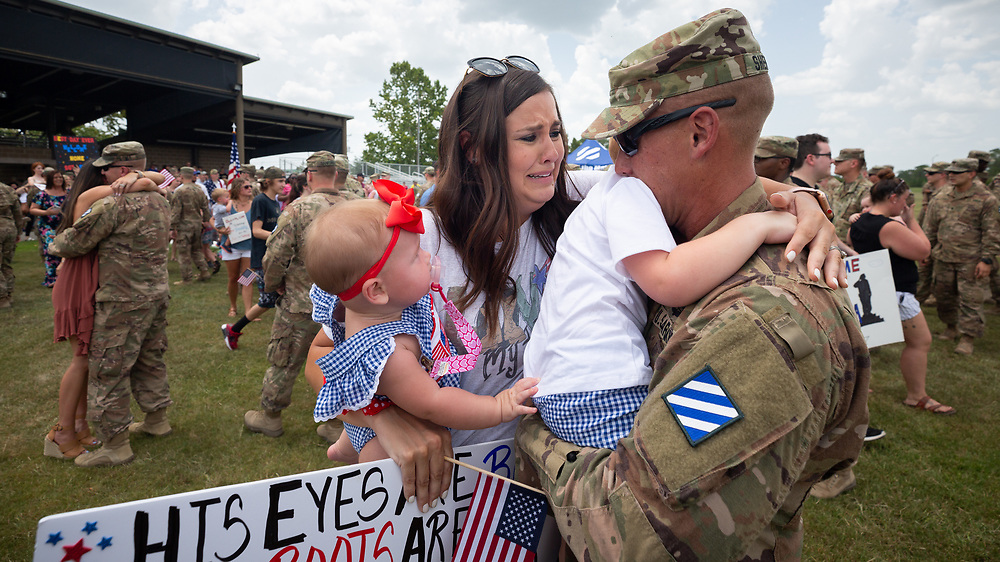 FORT STEWART, GA - JULY 17, 2019: Georgia National Guard Capt. Brice Sherfesee, of Carrollton, Ga., hugs his 2-year-old son Hudson, his wife Melissa Sherfesee and their 7-month-old daughter Hensley during a homecoming ceremony for the soldiers of the Macon-based 48th Infantry Brigade Combat Team Wednesday, July 17 2019 at Ft. Stewart, Ga. The unit finished a seven month deployment to Afghanistan in support of Operation Resolute Support. (AJC Photo/Stephen B. Morton)
