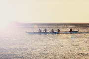 A crew of five row on the waters of the Pacific Ocean.