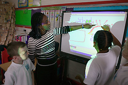 Teacher showing school children how to use interactive whiteboard in classroom,
