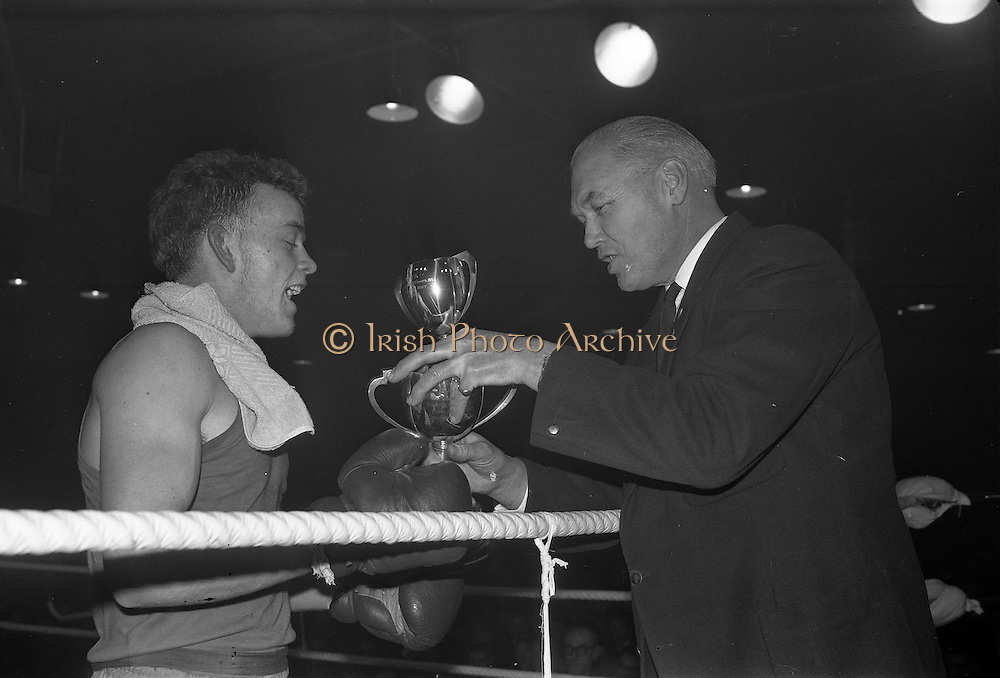 25/01/1963<br /> 01/25/1963<br /> 25 January 1963<br /> National Junior Boxing Championships at the National Stadium, Dublin. Picture shows Deputy Commissioner P. Carroll, President of the I.A.B.A., presenting the Pardon Trophy and replica for the light/welterweight Junior Champion of 1963 to W. Turkington of Doagh Boxing Club, after he beat P. Gaule of Kilkenny in the final.