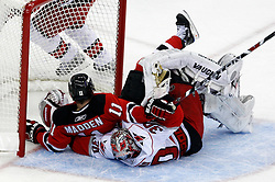 Apr 23, 2009; Newark, NJ, USA; New Jersey Devils center John Madden (11) knocks over Carolina Hurricanes goalie Cam Ward (30) during the first period of game five of the eastern conference quarterfinals of the 2009 Stanley Cup playoffs at the Prudential Center.