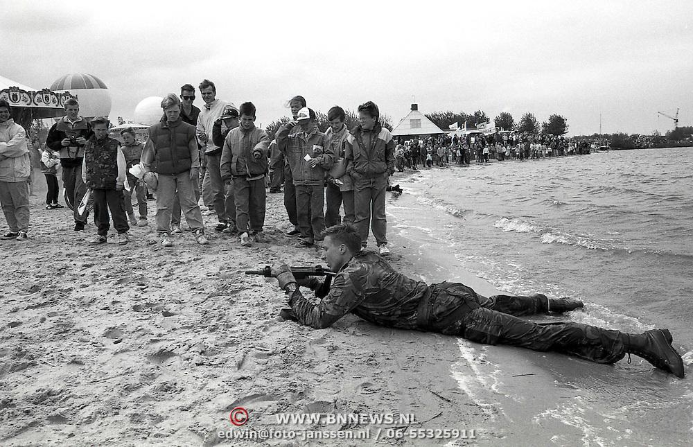 NLD/Huizen/19910525 - Waterspektakel Huizen 1991, landing op het strand van een marinier met een uzi