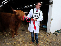 © Licensed to London News Pictures.14/07/15<br /> Harrogate, UK. <br /> <br /> A man leads his bull out of the sheds before going into the arena to compete on the opening day of the Great Yorkshire Show.  <br /> <br /> England's premier agricultural show opened it's gates today for the start of three days of showcasing the best in British farming and the countryside.<br /> <br /> The event, which attracts over 130,000 visitors each year displays the cream of the country's livestock and offers numerous displays and events giving the chance for visitors to see many different countryside activities.<br /> <br /> Photo credit : Ian Forsyth/LNP