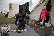 Nea Kavala, Greece - 23.03.2016  <br /> <br /> A man from Syria eating the warm meal which soldiers give them. 3,515 refugees are currently living in the official Greek refugee camp in Nea Kavala. The Greek military opened the 600 tents big camp about 1 month ago. The conditions in the camp are meager : In case of rain the area is partially submerged also the tents are not heated .<br /> <br /> Ein Mann aus Aleppo ißt eine warme Mahlzeit die das Griechische Militaer ausgegeben hat. 3.515 Fluechtlinge leben derzeit in dem offiziellen griechischen Fluechtlingscamp in Nea Kavala. Das griechische Militaer eröffnete das aus 600 Zelten bestehende Lager etwa 1 Monat vorher. Die Bedingungen im Lager sind dürftig: Bei Regen steht das Gelaende teilweise unter Wasser außerdem sind die Zelte nicht geheizt.