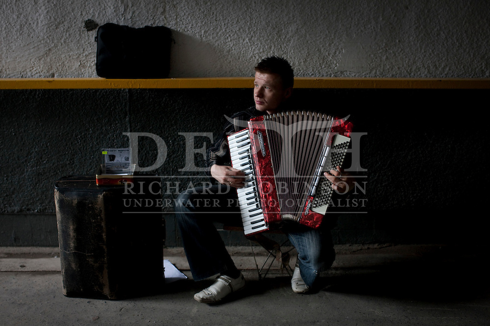 Accordion player in the underground passage on Targowa Street in the Praga district in Warsaw, Poland..Wednesday 12 May 2010.Photograph Richard Robinson © 2010.