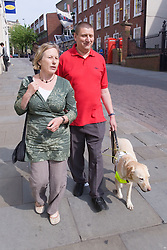 Vision impaired man with guide dog and sighted guide walking along a shopping street,