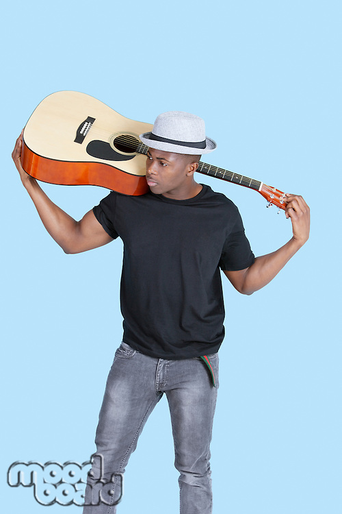 Young African American man carrying guitar over light blue background