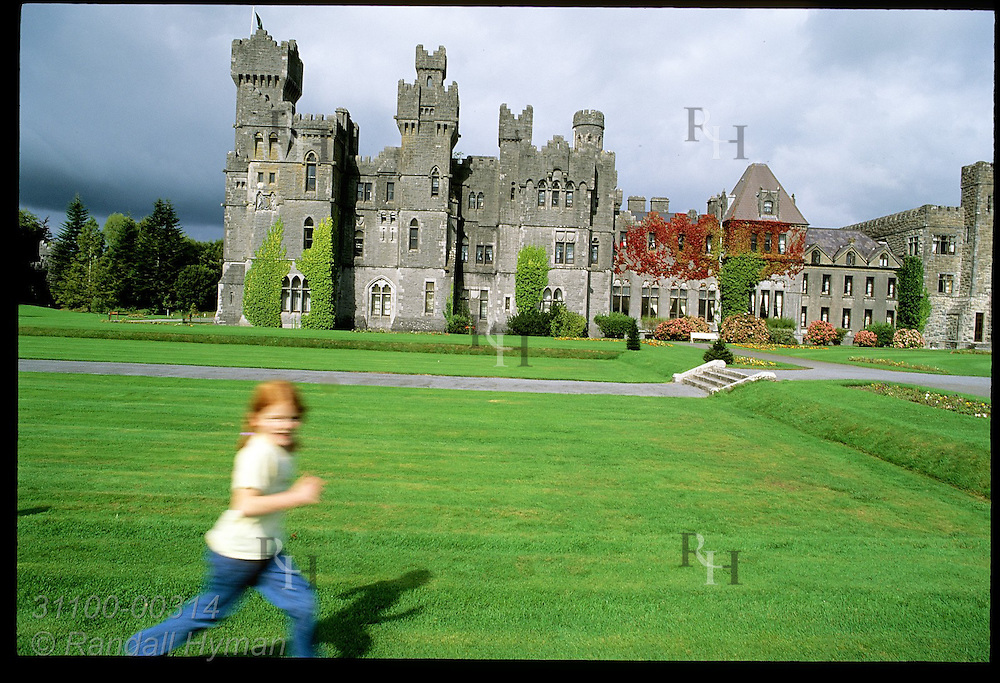 Girl runs in blur outside Ashford Castle, 83-room hotel with 13th-century roots now counted among Ireland's finest; Cong, Ireland.