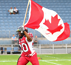 11.07.2011, UPC Arena, Graz, AUT, American Football WM 2011, Group B, Canada (CAN) vs Austria (AUT), im Bild Sammy Okpro (Canada, #20, DB) with the canadian flag // during the American Football World Championship 2011 Group B game, Canada vs Austria, at UPC Arena, Graz, 2011-07-11, EXPA Pictures © 2011, PhotoCredit: EXPA/ T. Haumer