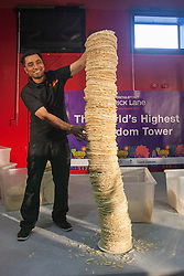 © licensed to London News Pictures. London, UK 20/07/2012. Raymam Miah, a cook from Poppadom Restaurant trying to break the world's highest poppadom tower record in Brady Arts and Community Centre. The 161cm tall tower managed to stand only 8 seconds but rules require 10 second to break the official world record. The record attempt was the part of the Curry Capital Festival in Brick Lane. Photo credit: Tolga Akmen/LNP