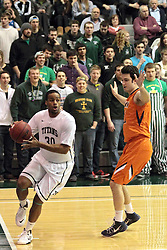 01 March 2014:  Eric Dortch turns in at the baseline engaging defender Joel Smith during an NCAA mens division 3 CCIW  Championship basketball game between the Wheaton Thunder and the Illinois Wesleyan Titans in Shirk Center, Bloomington IL