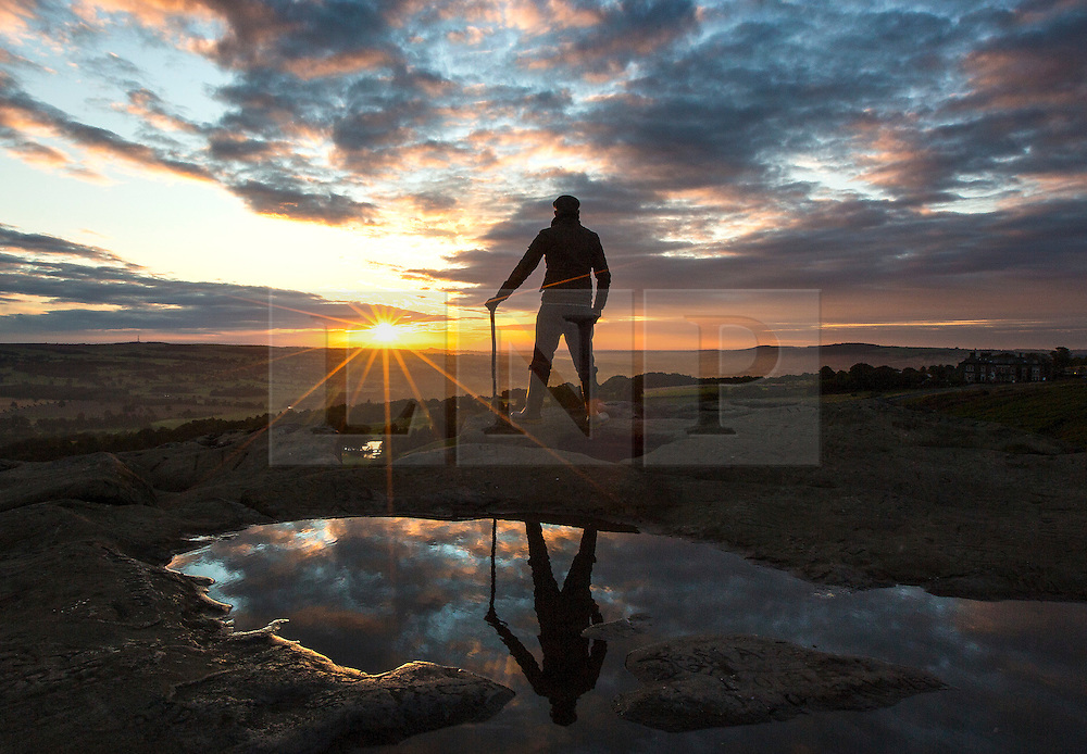© Licensed to London News Pictures. 02/09/2015. Ilkley, UK. Picture shows a man watching this mornings sunrise 1,319 above sea level on top of the Cow & Calf rocks at Ilkley Moor. Photo credit: Andrew McCaren/LNP