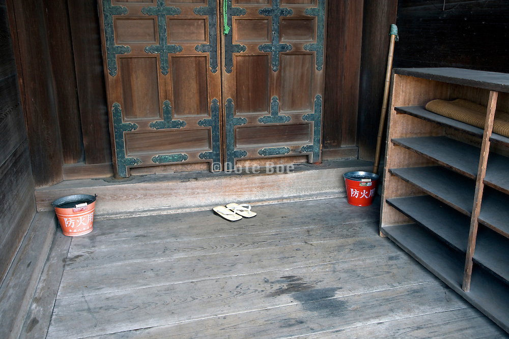 side door at the Nigatsu-do Hall of the Todai-ji temple In Nara Japan with 2 fire prevention water buckets