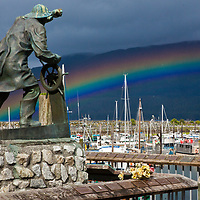 The Cordova Fisherman's Memorial looks out over a harbor rainbow in Cordova, Alaska on August 10, 2017.