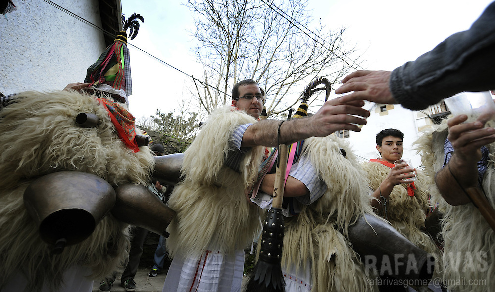 "A group of ""Joaldunak"" (""those who play the bell"") take a rest to drink some cider after marching carrying big cowbells tied to their backs as they take part in the ancient carnival of Ituren, in the northern Spanish province of Navarra province, on January 30, 2012."