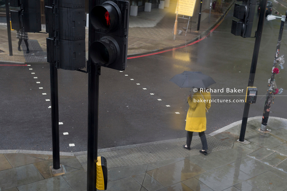 During a seasonal rain shower, a lady wearing a yellow coat pauses to cross the road at St. George's Circus in Southwark, on 9th May 2019, in London, England.