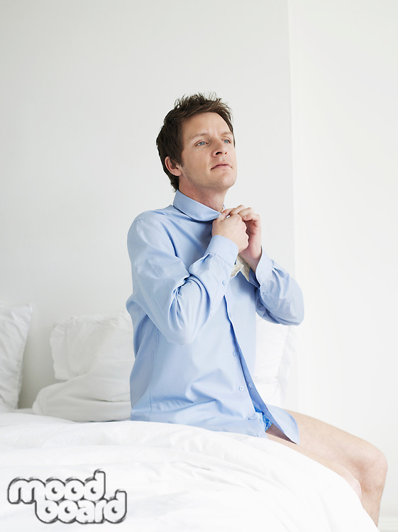Young man sitting on bed buttoning up shirt