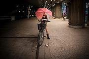 TOKYO, JAPAN, 13 APRIL  - Oimachi - 04-2012 - A young girl is sitting on her bicycle, hanging a pink umbrella on her shoulder. APRIL 2012 [FR]  Une jeune adolescente portant une tenue blanche à tache noire et des bottes tient un parapluie rose, et est assises sur son velo